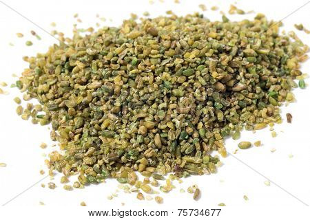 A heap of frikeh or freekeh grains on a white background. The cereal is made from immature, green wheat which is fire-roasted to make a healthy, low-glycemic-index food high in protein and minerals,