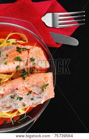 fresh fried natural pink salmon on italian traditional tagliatelle s backed with tomato and vegetables served over black wooden table high resolution hidef