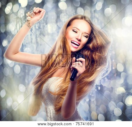 Beauty model girl with a microphone singing and dancing over holiday glowing background. Karaoke party singer. Disco party. Celebration