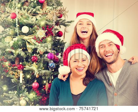 Happy Christmas Family portrait. Smiling Parents with teenage daughter at Home Celebrating New Year. Christmas Tree.
