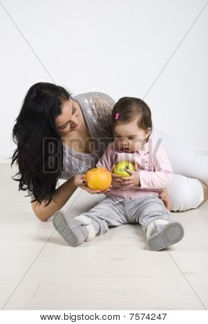 Mother Giving Fruits To Her Little Baby