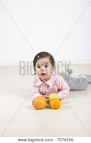 Toddler Girl Lying On Floor With Fruits