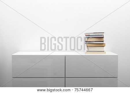 White Commode With Stack Of Books In Bright Minimalism Interior