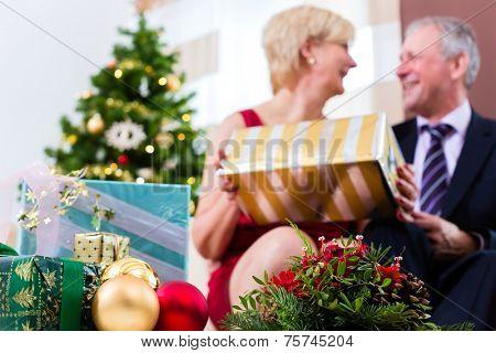 Senior man and woman celebrating Christmas with presents and X-mas tree