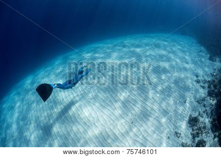Lady free diver swimming over sandy bottom with mono fin