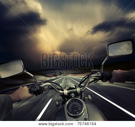 Rider on the motorcycle moving towards dark storm clouds. Road and sky are motion blurred
