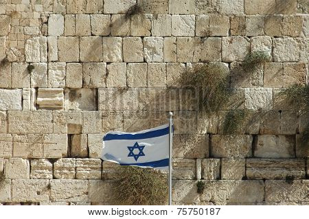 Stones of the wailing wall in Jerusalem with Israel's national flag