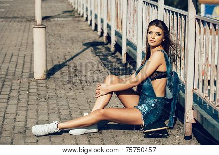 Beautiful Young Woman Sitting On Skateboard In Day