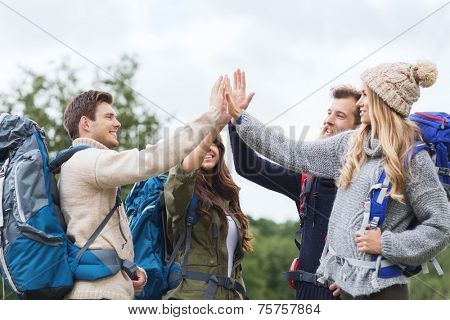 travel, tourism, hike, gesture and people concept - group of smiling friends with backpacks making high five outdoors
