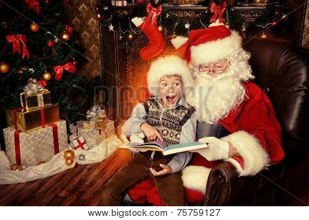 Santa Claus and happy boy sitting in Christmas room and reading a book. Christmas home d�©cor.