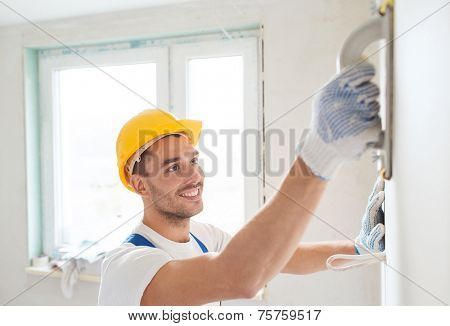building, profession and people concept - smiling builder in hardhat sanding wall indoors