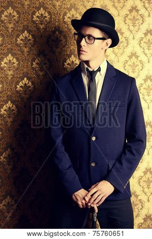 Portrait of a handsome young man in elegant suit and bowler hat posing over vintage background.