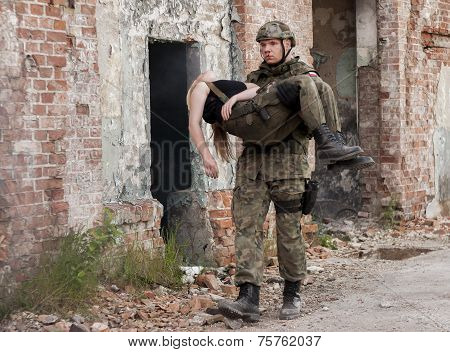 Wounded Woman And Soldier In Polish Army Uniform During  Historical Reenactment