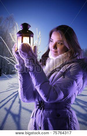 beautiful girl on winter snow with christmas lantern