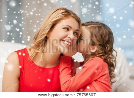 people, motherhood, family, winter and adoption concept - happy mother and daughter whispering something into ear at home