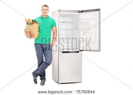 Full length portrait of a man with grocery bag standing by an empty fridge isolated on white background