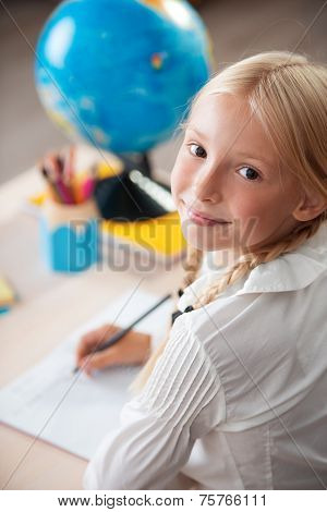 Smiling school girl sitting in classroom