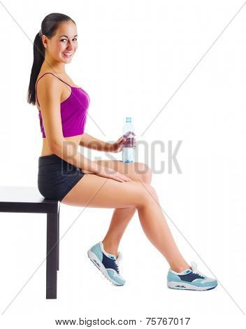 Young sporty woman with water bottle sit on the bench isolated