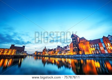 Gdansk old town and famous crane, Polish Zuraw. View from Motlawa river, Poland at romantic sunset, night. The city also known as Danzig and the city of amber. Sky copyspace