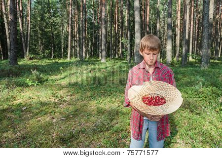 Boy Holding Straw Hat Full Of Red Wildberries