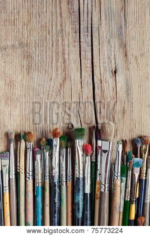 Row Of Artist Paintbrushes On Old Wooden Rustic Table