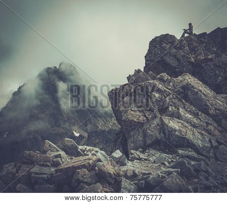 Woman hiker sitting on a mountain peak