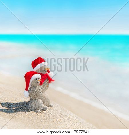 Snowmen Couple At Sea Beach In Christmas Hat. New Years Holiday