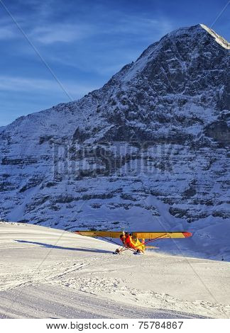 Yellow Red Airplane Landing At The Mountain Airfield In Swiss Alps