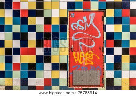 Red door in wall of colorful tiles