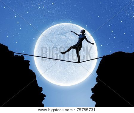 Young woman walking on rope above gap at night