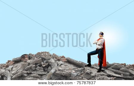 Confident super hero in cape and mask standing on ruins