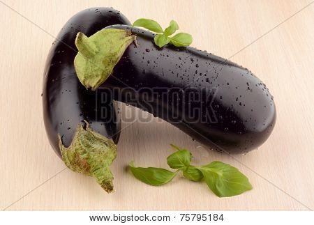 Pair Aubergines,eggplants With Basil Leaves On Bright Wooden Table