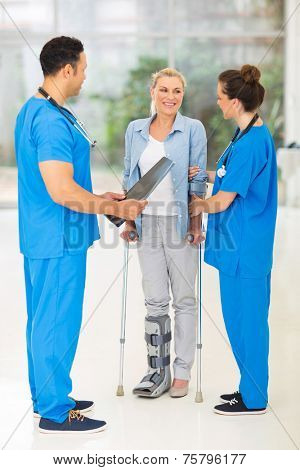 friendly healthcare workers with injured woman on crutches in hospital