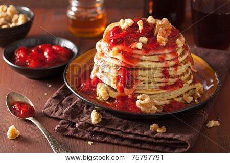 stack of pancakes with strawberry jam and walnuts. tasty dessert