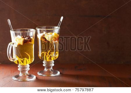 glass of mulled apple cider with orange and spices, winter drink background