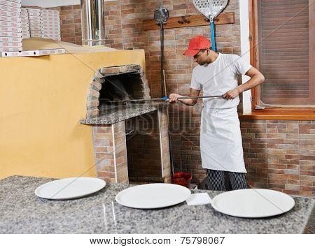 chef baker man in uniform making pizza at restaurant kitchen stove