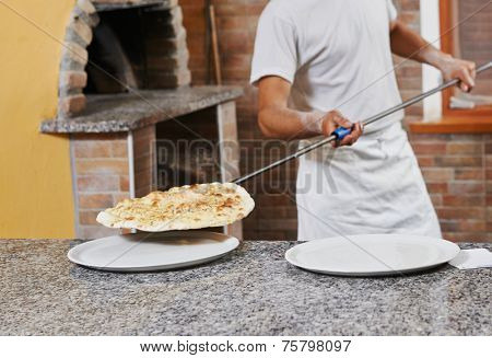 chef baker man in uniform making pizza at restaurant kitchen stove