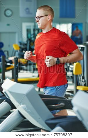 fitness man doing cardio-fitness by jogging at treadmill running training machine in gym