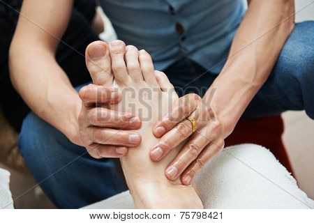 Masseur making a traditional chinese foot massage to adult leg and foot