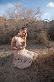 stock photo of bhakti  - Young woman in a beautiful dress kneeling in a secluded desert landscape - JPG