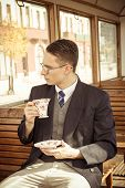 picture of wagon  - photo of man with glasses on train wooden wagon drinking coffee or tea from cup and looking through window retro vintage fashion photo - JPG