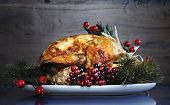 foto of give thanks  - Scrumptious roast turkey chicken on platter with festive decorations for Thanksgiving or Christmas lunch against dark recycled wood background - JPG