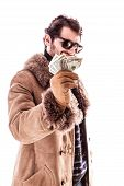 pic of hustler  - a young man wearing a sheepskin coat isolated over a white background holding banknotes