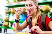 stock photo of bagpack  - European Woman eating at mobile kitchen stall on Jakarta travel exploring Indonesia street food - JPG