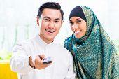 image of muslim man  - Asian Muslim man and woman watching television in living room - JPG