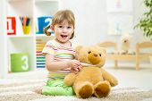 stock photo of girl toy  - child girl playing doctor with plush toy at nursery - JPG