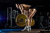 pic of snatch  - very brawny guy bodybuilder execute exercise deadlift with weight in gym - JPG
