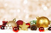 pic of twinkle  - Gold and red Christmas ornament border in snow with twinkling gold light background - JPG