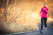 picture of fall day  - Young woman running outdoors in a city park on a cold fall - JPG
