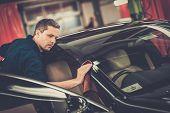 pic of luxury cars  - Man worker polishing car on a car wash - JPG